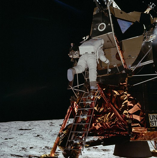 "Astronaut Edwin E. Aldrin Jr., lunar module pilot, egresses the Lunar Module (LM) ""Eagle"" and begins to descend the steps of the LM ladder as he prepares to walk on the moon"